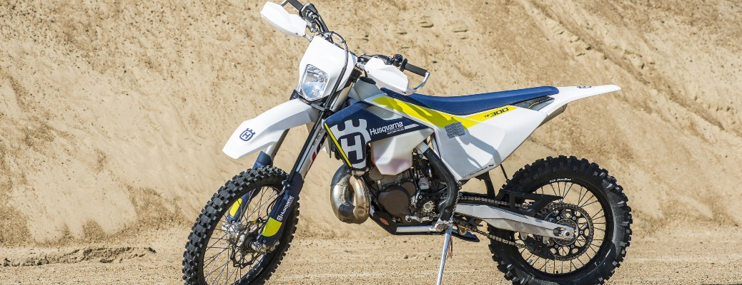 The side view of a white 2017 Husqvarna motorbike with a single-cylinder engine.