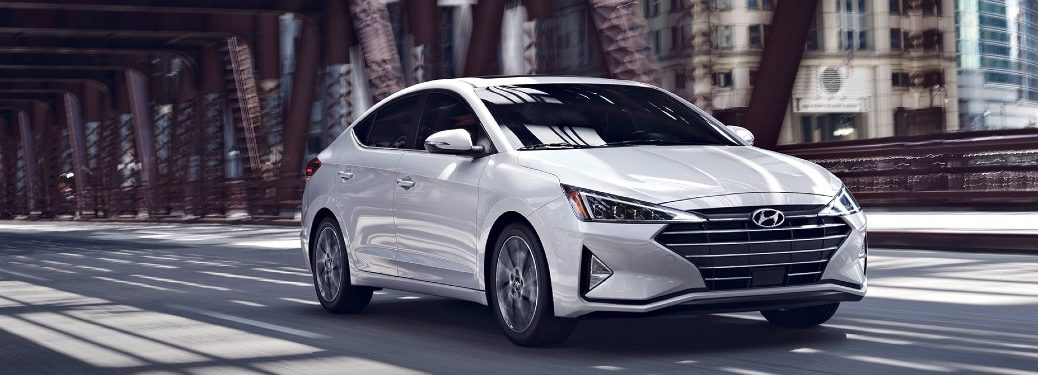 Front passenger angle of a white 2020 Hyundai Elantra driving on a road