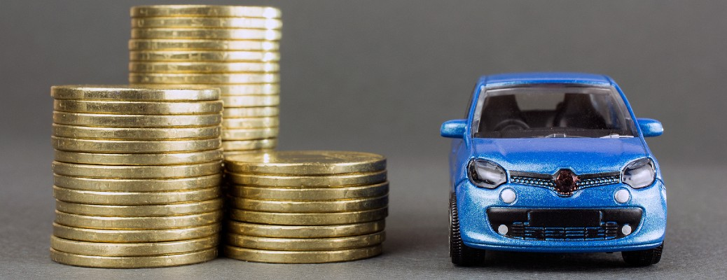 Three stacks of coins next to a small blue vehicle