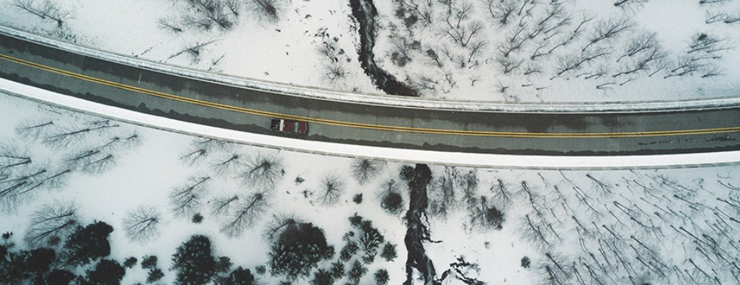 A road with a car driving on it as seen from the sky. Snow is on both sides of the roadway