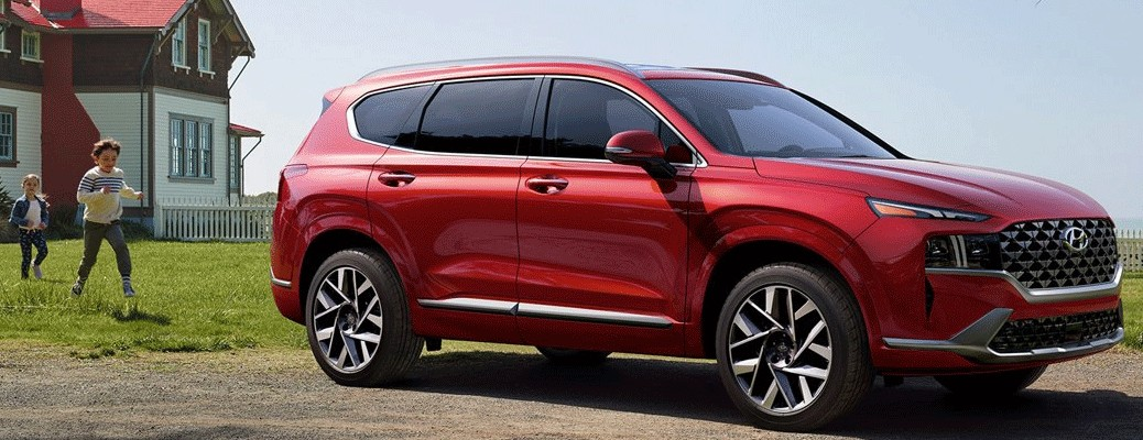 A red-colored 2021 Hyundai Santa Fe parked outside with two people walking toward it with a house in the background