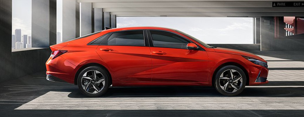 A red-colored 2021 Hyundai Elantra parked inside a building with several windows