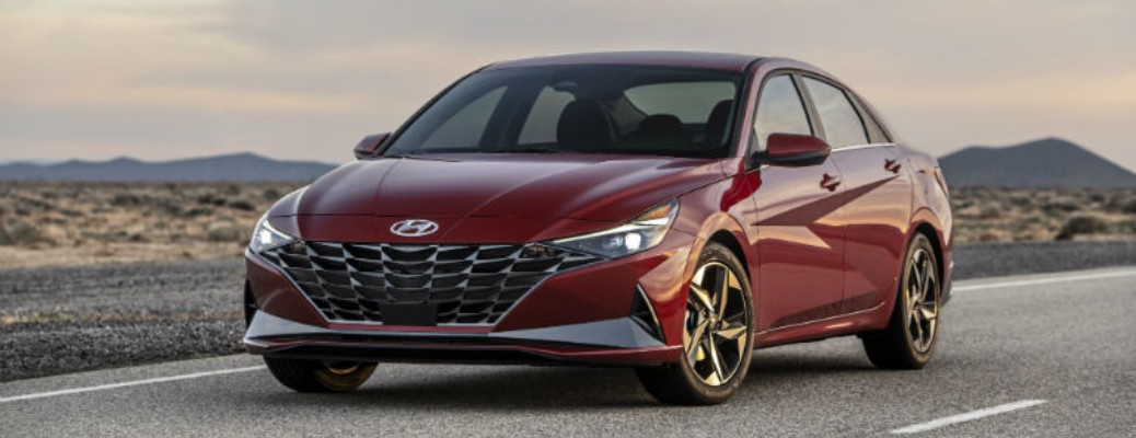 A red-colored 2021 Hyundai Elantra driving on a road