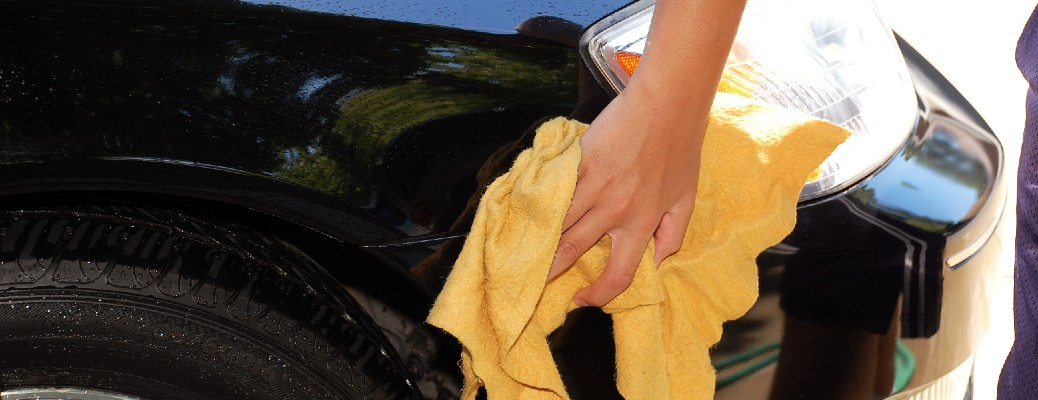 A person with a yellow towel cleaning a car