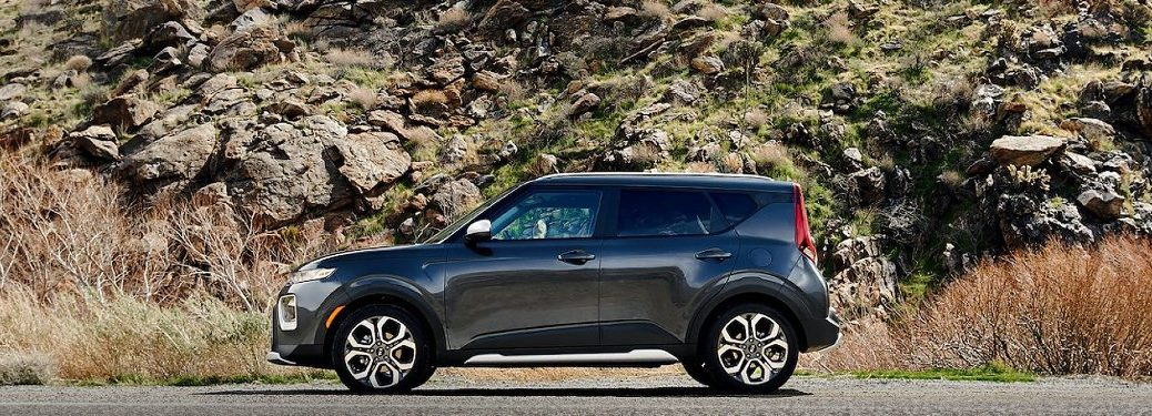 2021 Kia Soul black exterior driver side parked in front of rocky hill