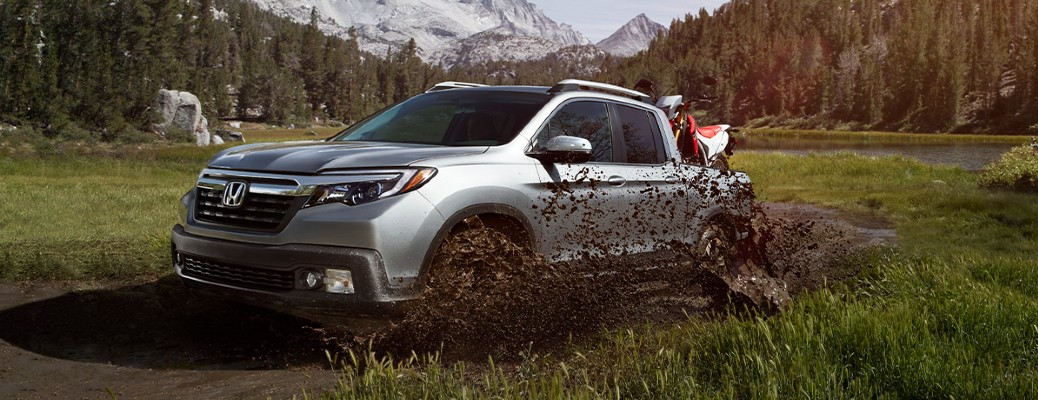 2020 Honda Ridgeline RTL gray exterior front driver side driving in muddy area in forest