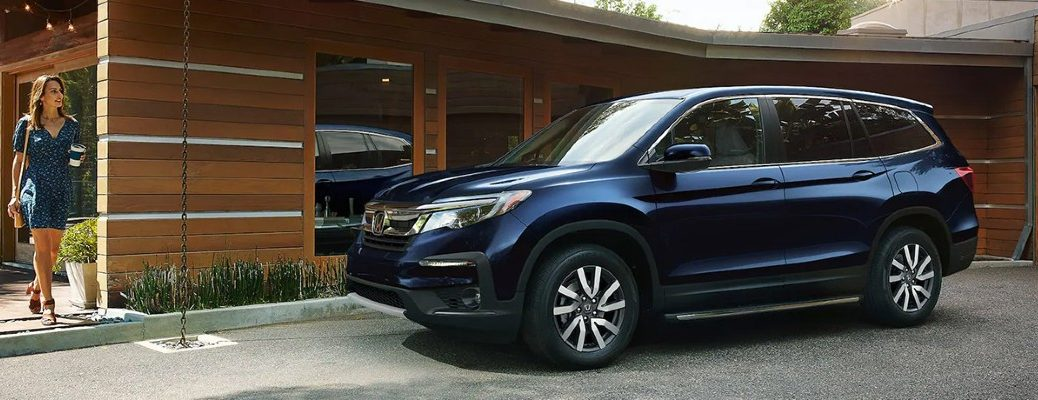 2021 Honda Pilot blue exterior front driver side parked outside of house woman in dress walking out