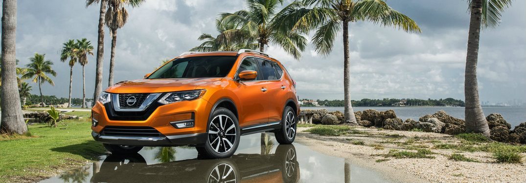 Orange 2018 Nissan Rogue parked in front of palm trees on a sunny day