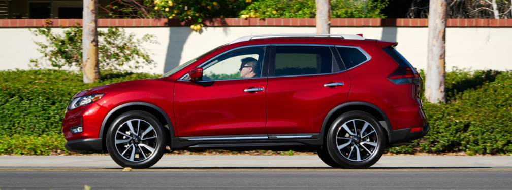 Side view of red 2020 Nissan Rogue parked on the street
