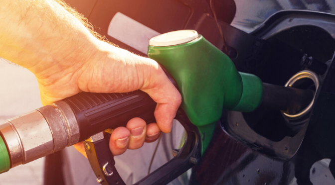 Closeup of hand holding gas pump to vehicle