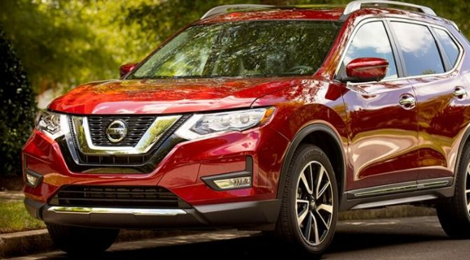 Red Nissan Rogue on a leafy street