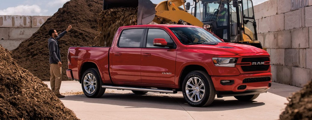 2021 RAM 1500 1500 with a man standing next to it directing a digger