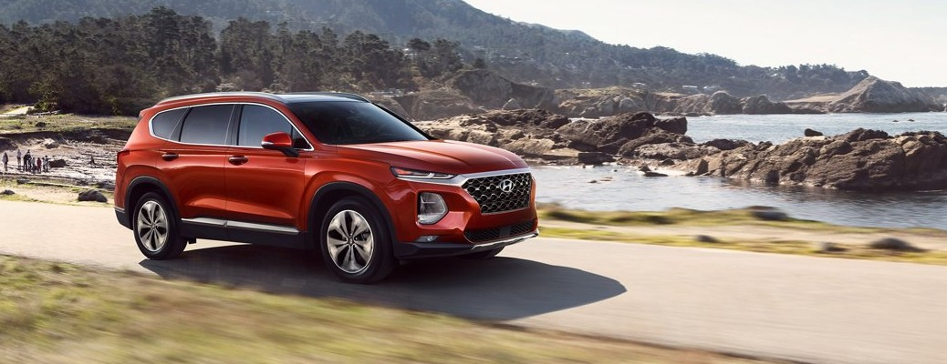 2020 Hyundai Santa Fe red driving near rocky bay on pavement with grass