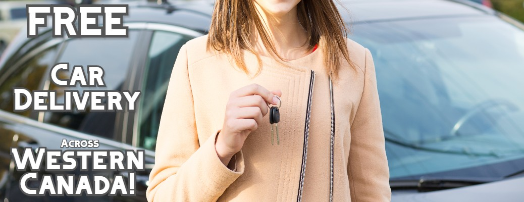 stock photo of woman handing off keys in front of car free car delivery across western canada