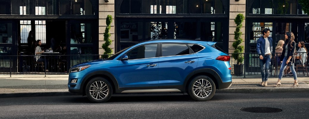 2021 Hyundai Tucson blue profile view parked on street in front of building