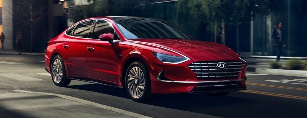 A stunning red-colored 2021 Hyundai Sonata Hybrid driving in the downtown streets with blurry trees and people in the background