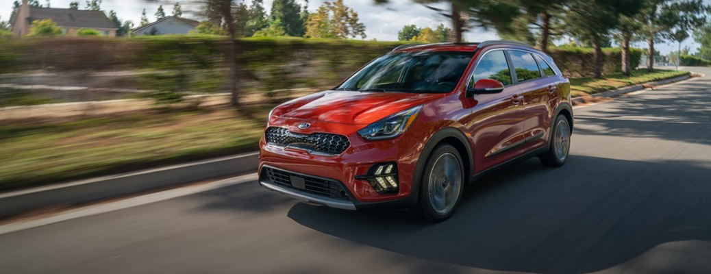 2020 Kia Niro red driving with motion blur past trees and bushes