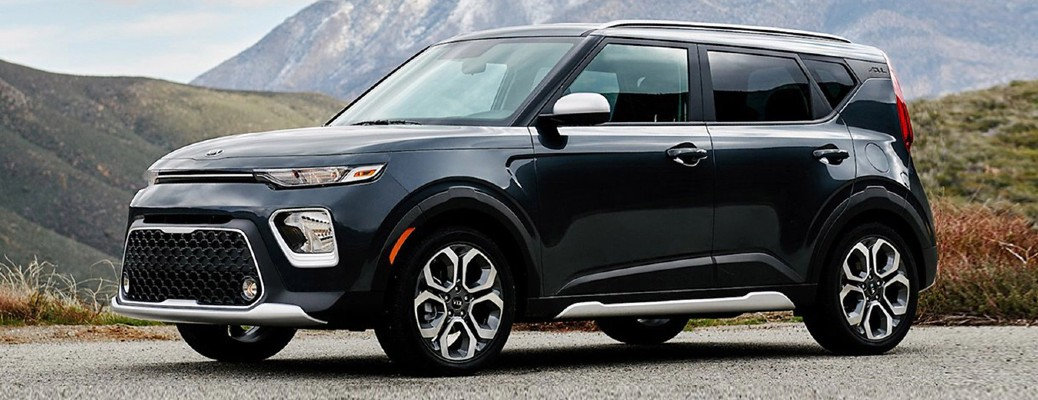 2021 Kia Soul dark blue parked on gravel in front of hills and mountains
