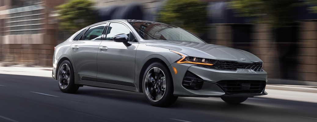 2021 Kia K5 grey driving in city with motion blur showing passenger side