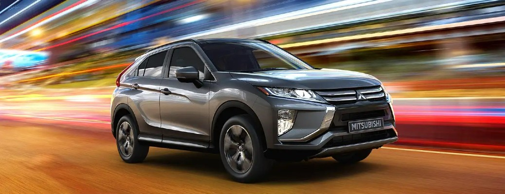 2020 Mitsubishi Eclipse Cross grey driving past bright blurred lights