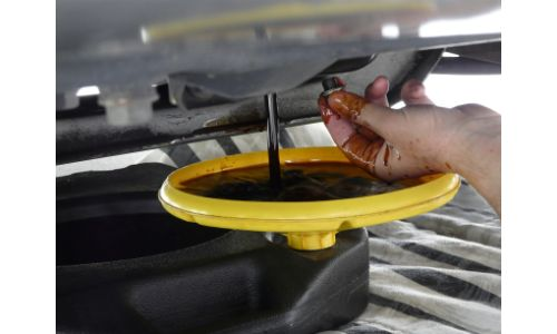car oil being drained into yellow oil pan