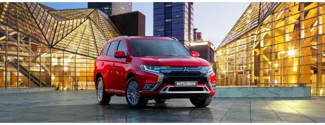 2020 Mitsubishi Outlander PHEV red parked in front of glass buildings with yellow light