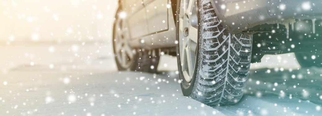 car driver in snow close up on back tire