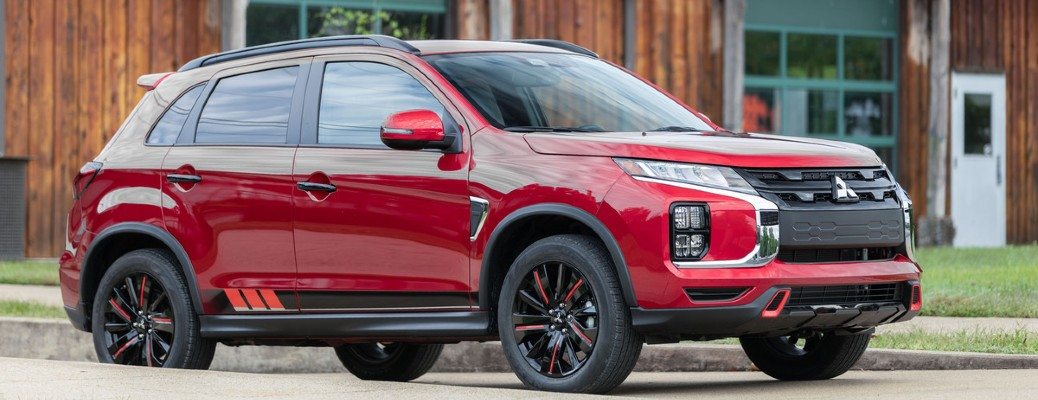 2021 Mitsubishi RVR red with decals in front of wood building
