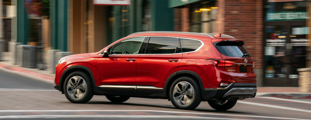 Side view of red 2020 Hyundai Santa Fe driving