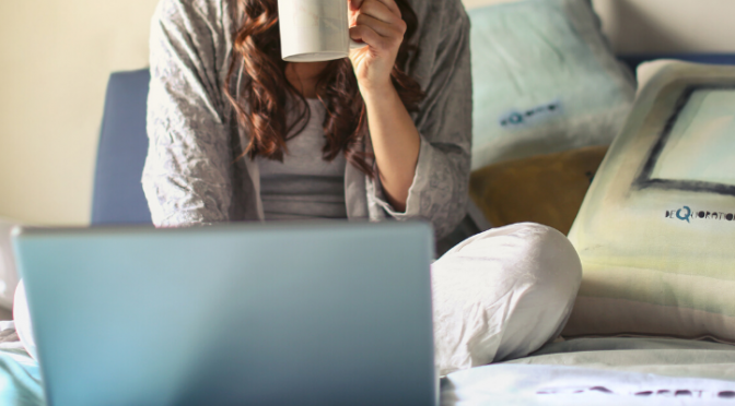 Woman holding coffee cup and using laptop