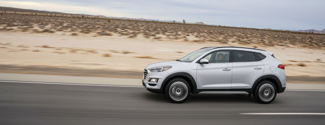 Side view of silver 2021 Hyundai Tucson driving