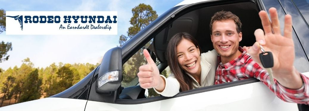 Happy Couple in a New Car with Keys and Rodeo Hyundai Logo