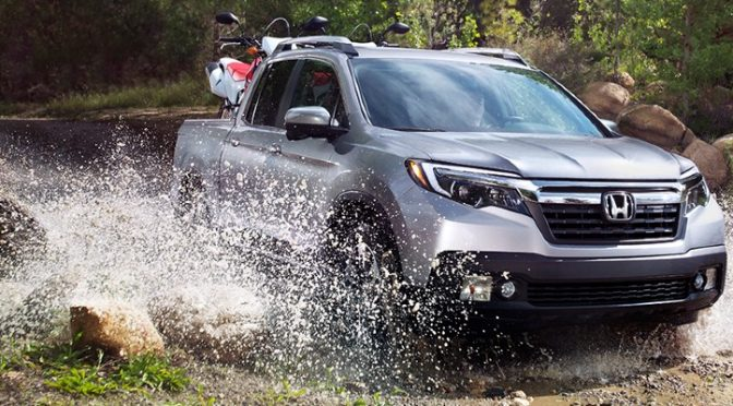 2020 Honda Ridgeline grey exterior front passenger side driving through water in wooded area