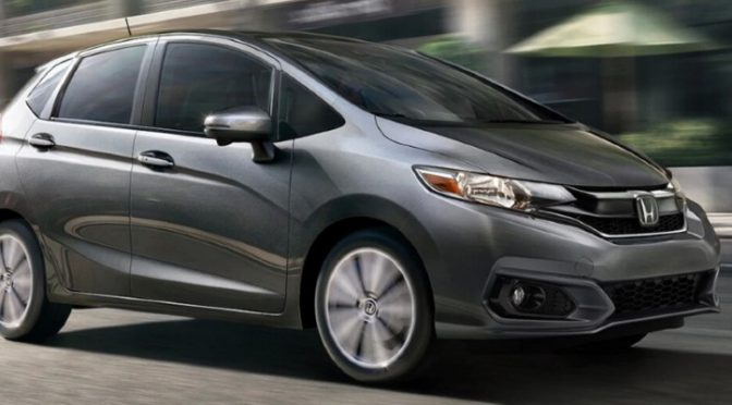 2020 Honda Fit grey exterior front passenger side driving in city past restaurant patio_o