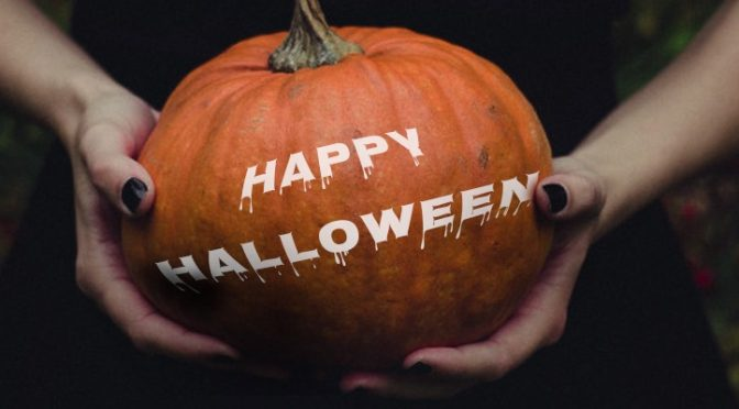 Person holding pumpkin with Happy Halloween text