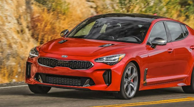 front left view of red kia stinger driving