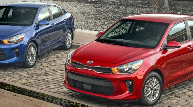 blue and red kia rio parked next to water