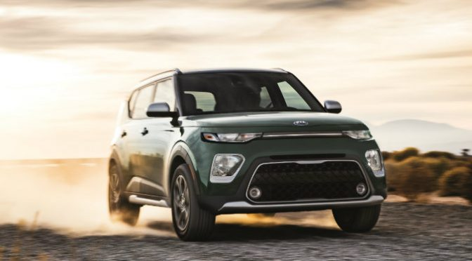 dark green kia soul driving on dirt