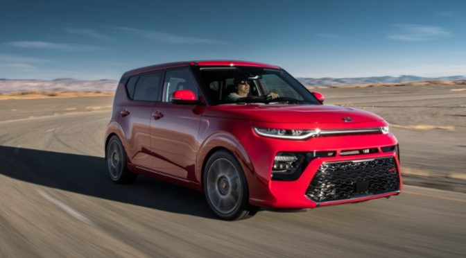 right-front view of red kia soul driving