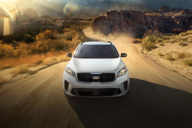 White 2020 Kia Sorento driving down dirt road from exterior front