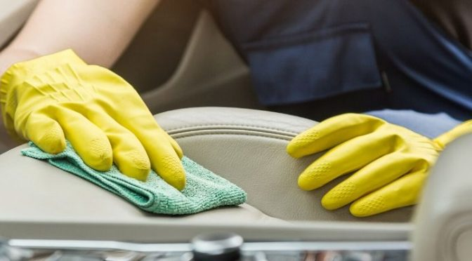 Mechanic cleaning interior of car
