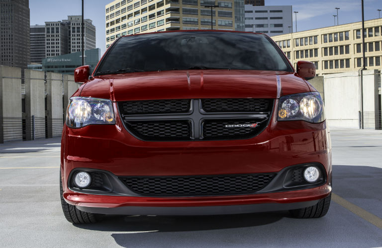 The front side of a red 2018 Dodge Caravan.