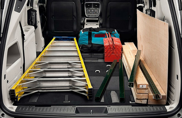 The rear interior of a three-row 2018 Dodge Grand Caravan packed with long, narrow work equipment.