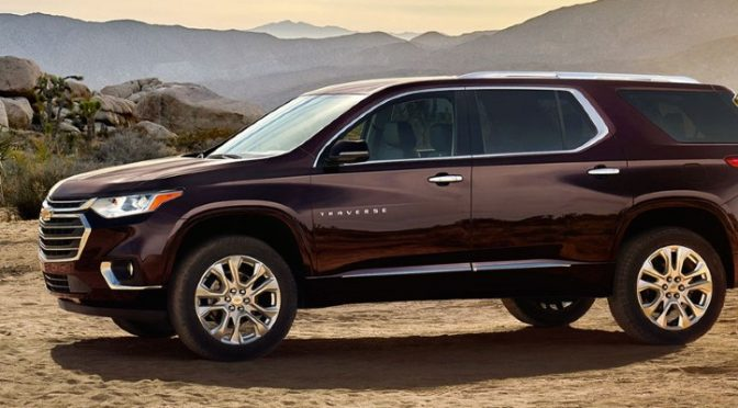 A three-row burgundy 2020 Chevrolet Traverse SUV parked in a hilly, desert-grassland environment.