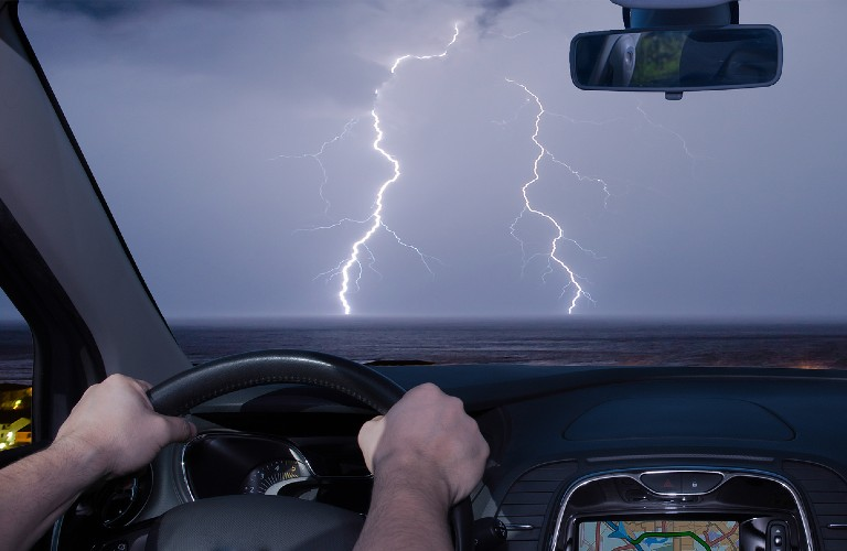 A person driving close to a storm with lightning touching the ground.