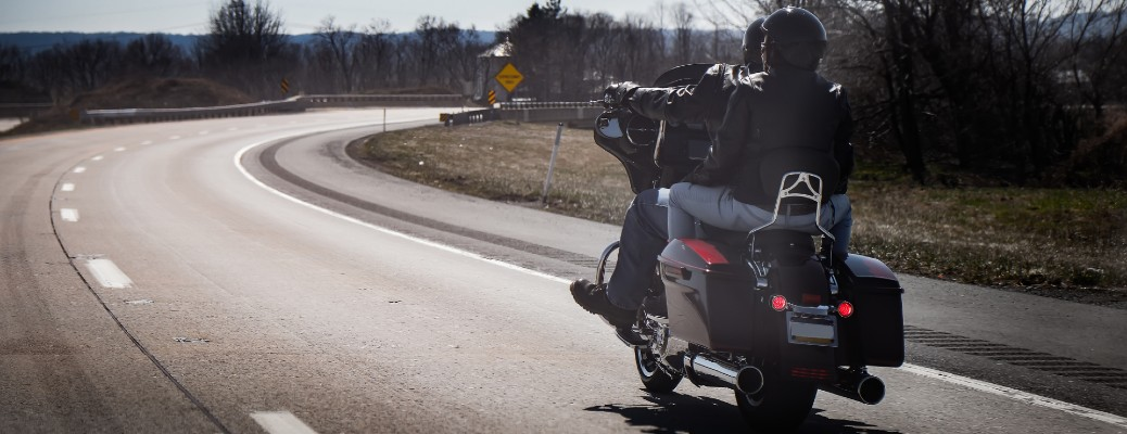Two people riding on a motorcycle that is moving down the open road.