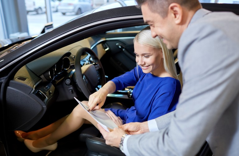 A vehicle salesman talking to a young woman sitting in a new vehicle.