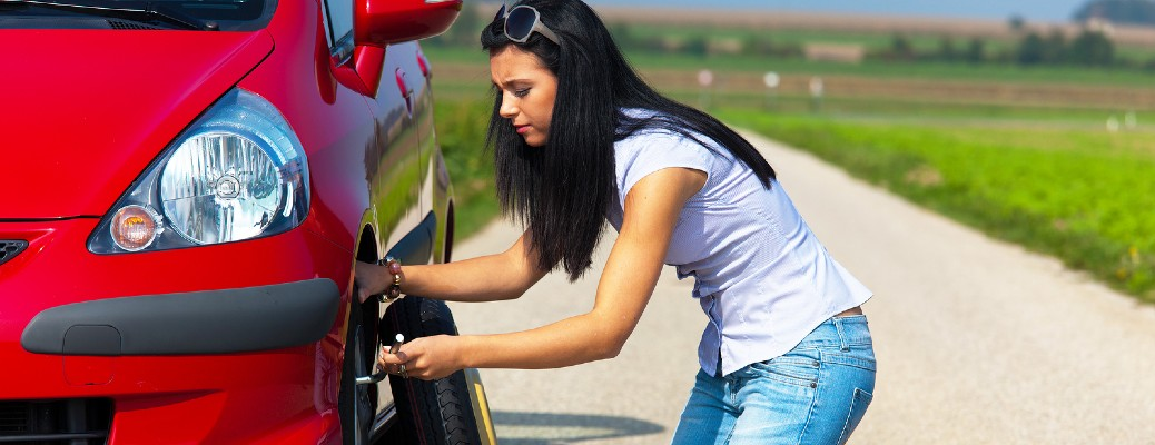 A young woman changing the tire on her car on the open road.