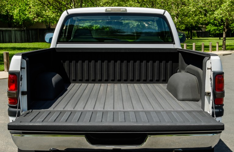 The rear view of a white truck with an empty truck bed.