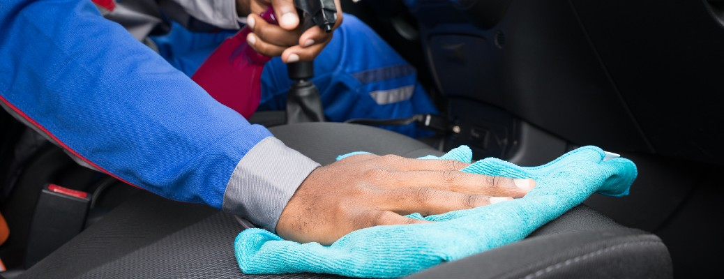 A man cleaning the interior seating in a vehicle with a blue cloth.